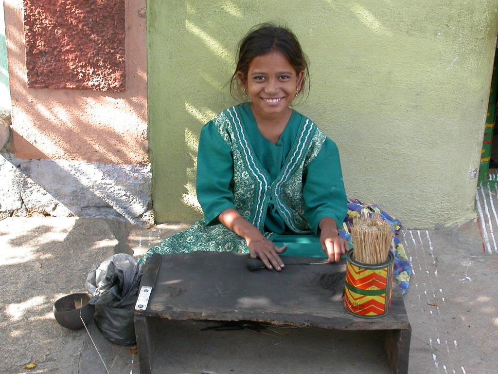 Sitzendes Kind das arbeitet und Räucherstäbchen herstellt. (Quelle: 1x1 für Indien)
